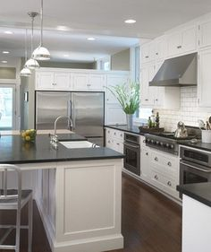 White cabinet, subway tile, dark floors, dark counters, island - and check out the fridge wall that has open space above