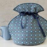 Tevarmer.. Tevarmer i blå nuancer. Bindes fast på tekanden, så man kan bære potten rundt uden teen afkøles.. Pris 270,- kr.