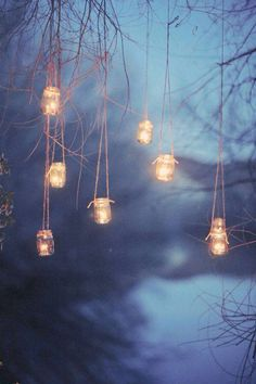 Mason jars, twine, lace ribbon, pine branches and a battery tea light, hang in the trees