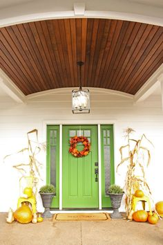 white farm house with a green front door and stained wood barrel vault entry