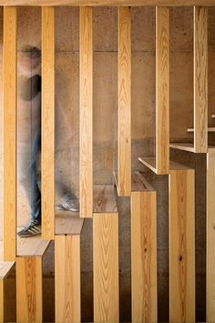 The pine panels used for the concrete form work were subsequently cleaned and planed so they could be reused internally as floorboards, walls and built-in furniture. The architects claim that 93 per cent of the wood has been reused in the project.  A second flight of stairs continuing to the top floor is designed with open treads formed at the junction of vertical balustrades, which rise up from the floor and descend from the wall above.