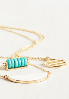 Bopping from here to there is all the more enjoyable in this tiered necklace. The three long chains of this adjustable accessory flaunt different fab features, like a row of faux-turquoise beads, a unique gold charm, and a hemisphere pendant with ivory iridescence. How elegant!