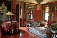 The second-floor landing is furnished with Hempel-designed daybeds upholstered in velvet; the large portraits are both 17th-century English School, while the mirror is Regency | archdigest.com