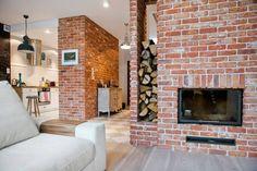 Czerwone cegły i kominek w salonie - Lovingit.pl