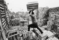 1990. En la Central de Abasto los acomodadores de huacales construyen todos los días una ciudad efímera de geometría caprichosa, que nace y muere en unas horas. Surge en la madrugada con las primeras descargas y se desvanece al atardecer, cuando la guerra del mercado pacta una frágil y cotidiana tregua. Foto: Raúl Ortega