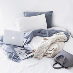 Cozy vibes in bed with grey knitted blankets, pillows, a purse, and a Macbook » Sunday work mode