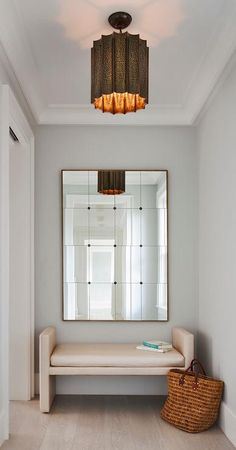 Light gray wash wood floor lead to a cream foyer bench placed beneath a French multi-panel mirror illuminated by a copper light pendant hung from a tray ceiling framed by white crown molding.
