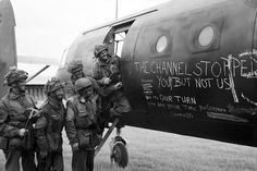 """""""Now it's our turn."""" Airborne troops admire the graffiti chalked on the side of their glider as they prepare to fly out as part of the second drop of the night on June 6, 1944"""