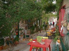 La Garde-Adhémar: Ruelle du village avec tables et chaises colorées d'une terrasse de café, arbustes et ornements anciens, notamment une vieille bicyclette, en Drôme provençale - France-Voyage.com