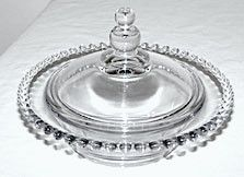 This is an Elegant Glass covered candy or jelly dish in the Candlewick pattern made by Imperial. It measures 6.5 inches across with the cover measuring 5.5 inches wide and is in very nice condition wi
