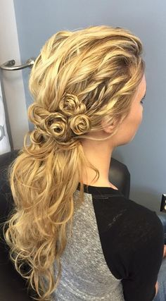 Stunning look created by Stephanie Knutson! She used a 1-inch curling iron then broke up the curls with a large tooth comb. She then did small braids to make a floral accent in the hair. She used #Kenra Design Spray 9 and finished with Volume Spray 25 and Shine Spray. #WeddingHair #Braids