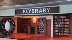 """Una biblioteca en el Aeropuerto Internacional de Ciudad del Cabo.  El Flybrary fue inaugurado en julio con mayoría de libros de segunda mano y está abierto a los pasajeros y a los miembros del aeropuerto. """"El Flybrary"""" es la única """"biblioteca aeropuerto"""" abierta de Sudáfrica. Se insta a los viajeros a cambiar su libro terminado por otro."""