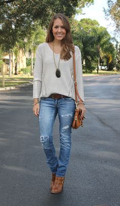 loose ivory knit pullover sweater + distressed jeans + brown belt + cognac ankle boots + long chunky pendant necklace