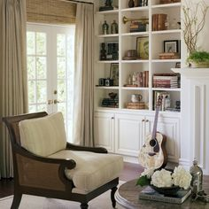 bookcases. display.  white trim work.  cane chair.  double window treatments.