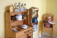 I like the hanging shelf next to the kitchen, and the doll highchair in the corner-- image via Frontier Dreams: Kitchen View : the Girls' Corner