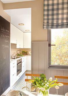 Del office hacia cocina con suelo hidráulico. Office en tonos claros con una gran pizarra que conecta con la cocina