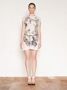 Markus Lupfer Framed Garden Embellished Dress. Sheer cream dress with a frayed edge neckline and sleeve detail, features an all over front graphic print with embellished and appliqué detailing. The frayed edge back with a deep scoop and darts is completed with an adjustable rope tie tassel detail. 100% Virgin Wool.