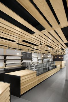 Wood slats add warmth to the otherwise monochrome interior of this bakery and coffee shop in Montreal by local architects Naturehumaine. Design Shop, Bakery Shop Design, Coffee Shop Design, Deco Design, Shop Interior Design, Restaurant Design, Retail Design, Store Design, Modern Restaurant