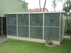 Four single aviaries joined together seen here in a garden setting.