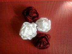 Botões de rosas em fitas de cetim ou seda.