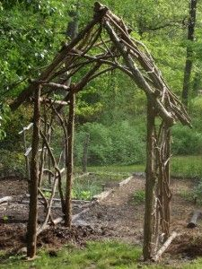 An arbor hand made of tree limbs.