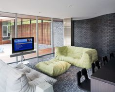 Modern family room with delicate curved walls and matching togo sofas