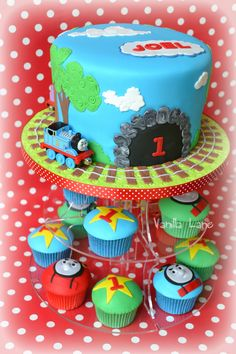 "Children's Birthday Cakes - ""All Aboard.........."" Thomas cake with matching cupcakes. Cake was vanilla cake with vanilla buttercream. Matching vanilla cupcakes with vanilla buttercream and then fondant :)"