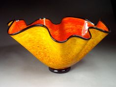 Hand Blown Glass Wave Platter Bowl-Large. Has a cherry red interior and a beautiful brilliant exterior and is finished with a black lip wrap and a black foot