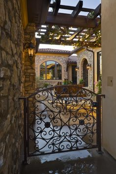 La Bella Vita @ Solterra 2008 Metro Denver Parade of Homes - The iron gate leads into a picturesque courtyard  sheltered by a pergola.