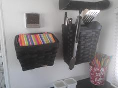 Inexpensive spraypainted baskets (or Longaberger's) mounted on wall for cooking utensils, knives, napkins, potholders, etc.