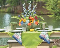 Spanning hues of blue and green, vivid table linens echo the natural surrounds, while stunning blooms in the centerpiece burst forth in a rainbow of color. #southernladymag #tabletopinspo #tabletop Southern Ladies, Centerpieces, Table Decorations, Table Linens, Pretty Flowers, Shades Of Green, Tablescapes, A Table, Floral Design