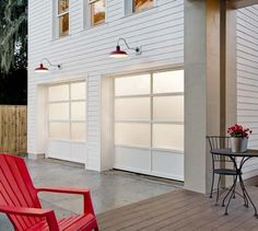 Avante Collection glass garage doors look right at home on this farmhouse. The red gooseneck lamps add a fun pop of color. Doors shown combine frosted glass and solid aluminum panels.