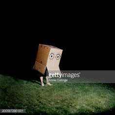 Stock Photo : Man standing inside large cardboard box with eyes painted on, night