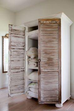 Boekenkast met oude shutters als deuren.