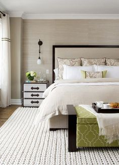beige, black and green bedroom // not a fan of the nightstand, but everything else is fairly simple and textured // the wall light next to the bed looks like a dangling cat toy, though!
