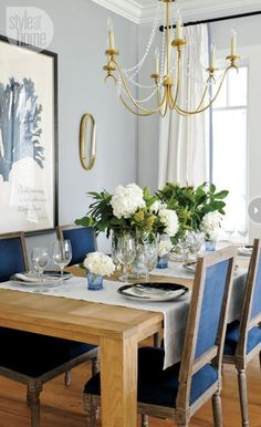 Brass chandelier, rustic wood farmhouse table, pale blue walls, coastal dining room