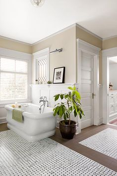 A wainscot cap alongside the tub is extra-deep to form a shelf for candles, cocktails, and other necessities. Tub: Waterworks