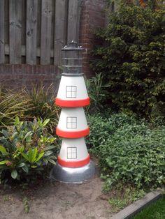 Deze vuurtoren is gemaakt van Bloempotten. En de bovenkant is een tuinlantaarn.