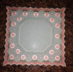 Unique Hardanger Embroidered Centerpiece    This Centerpiece was hand stitched by myself on a light green 25 count quality material with 3 shades of coral, light & dark greens DMC perle cotton color combinations!  It measures a perfect size of 12 x 12 square with a creative border.    The doily fits all furniture styles and looks very decorative on a table or nightstand.    If youre looking for a gift for someone who is hard to find things for, this doily would be a perfect choice…