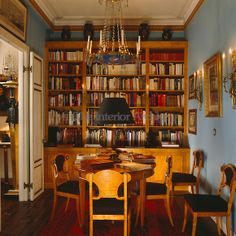 A library which alternates as a dining room, with Biedermeier bookcase, table and dining chairs