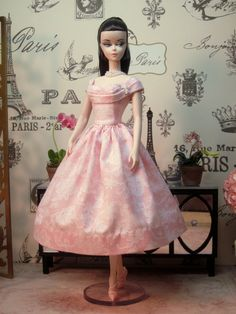 A classic Rockabilly dress in a feminine print of white lace on a pink ground. The bodice is sweetheart, with a pleated band that goes under