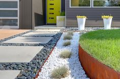 Crushed marble and river rock, which play off the hues of the home, mingle with easy-to-maintain blue fescue and sedum.