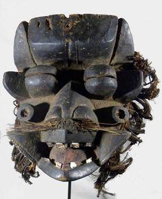 GRAND MASQUE WE (Côte d'Ivoire) En bois à patine brun-noir, les yeux sont globuleux, la bouche grande ouverte laisse apercevoir des dents en aluminium ainsi qu'une langue peinte en rouge. Autour du visage une collerette de fibres est fixée par des clous. Artcurial Lyon - 15/12/14