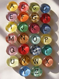 "There are so many possibilities when making alphabet magnets like this. Here I used ""western"" themed alphabet stickers I found at a craft store and stuck them onto to paper that looks like old jeans. Then glued a magnet on the back & a large clear stone on the front and voila! Another option (Shown here) uses plain black lettering & different paper backgrounds. Same idea, whole new look!"