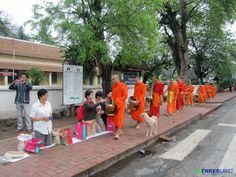 Threeland Travel Indochina  has taken this picture from our Laos trip early last month.   The tak bat, or the Buddhist monks' morning collection of food, so-called morning alms-giving, has become a must-see for travelers to Luang Prabang in Laos. This tradition manifests as a morning ritual where monks silently line the streets while locals (and interested tourists) put gifts of food into the bowls carried by the monks.