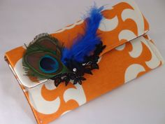 This Clutch is Made of a beautiful orange  cotton fabric its full lined in brown  cotton .  This clutch has a Velcro closure to keep your items secure. It is adorned with peacock feathers and a black Venise lace, I also added a genuine clear Swarovski crystal to finish it off.    Great for everyd...