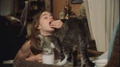 Brooke Shields and cat share cookies and milk.