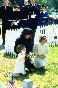 Jacqueline Kennedy with Caroline and John Jr put flowers on John F. Kennedy's grave after the funeral, 1963.