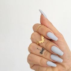 tattoo on the ring finger of a hand, wearing several golden rings, and pale creamy grey nail polish, on matte coffin nails #nailscoffin