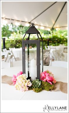 Lantern centerpieces adorned with flowers. Romantic and elegant.